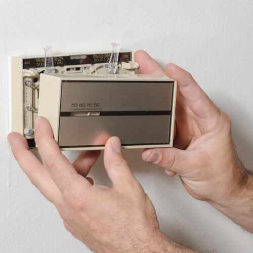 Older model of thermostat being taken off the wall.
