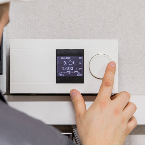 Programmable thermostat being adjusted.