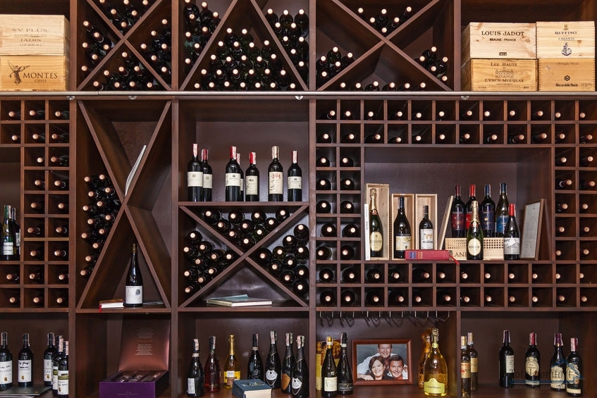 The bottles of the vein are laid out on the shelves. Bottles of wine on the shelves.